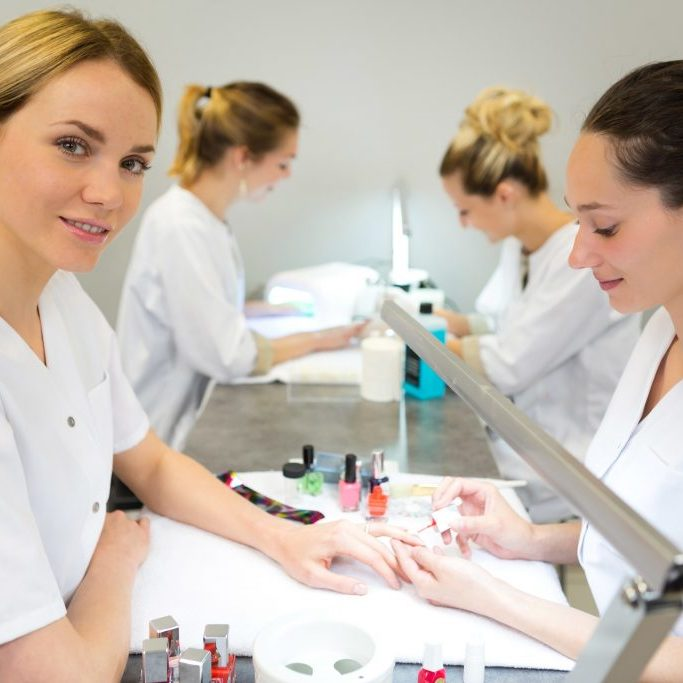 View of Young attractive beautician students practising during courses